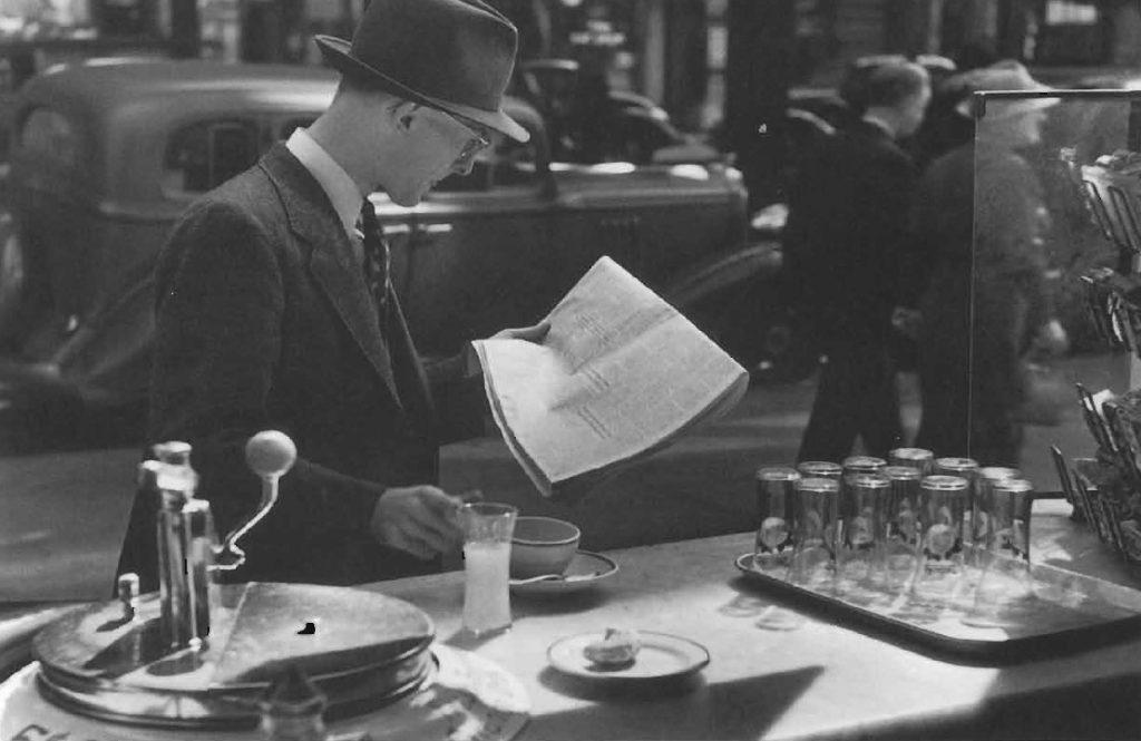 Petit déjeuner à l'américaine: café, jus de fruit, et lecture du journal au comptoir d'un étal de rue, vers 1949.